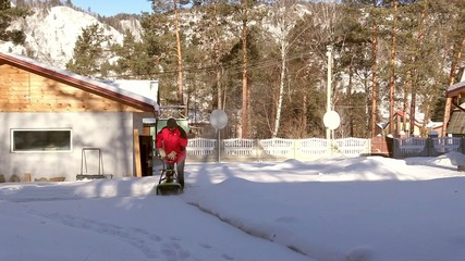 Young man removes snow near the house