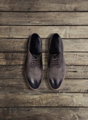 Brown men's shoes on a wooden background
