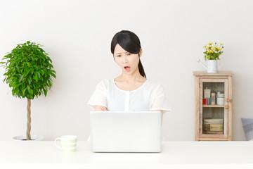 パソコンの前で怒る女性