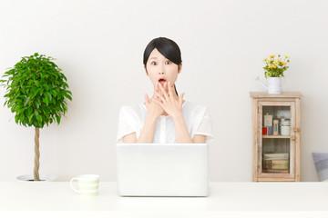 パソコンの前で驚く女性