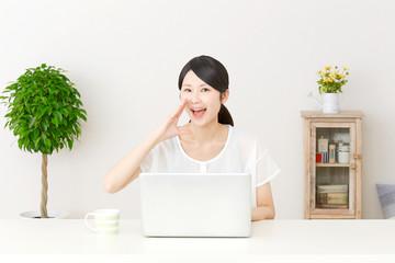 パソコンの前で呼びかける女性