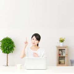 パソコンの前で指差す不安な女性
