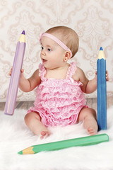 Adorable little baby girl with big crayons
