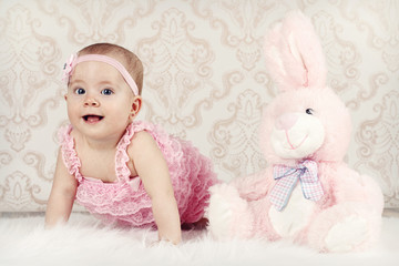 Little baby girl with pink plush rabbit