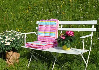 Gartenbank mit bunten Kissen