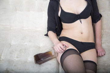 Sexy woman in black underwear holding bottle of whiskey