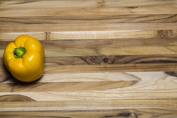 Yellow Pepper on a teak cutting board