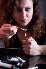 woman preparing drugs on teaspoon