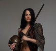 Goregeous female warrior poses holding sword and helmet