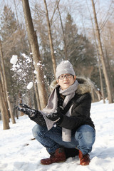 Asian handsome guy throwing snow in the air in garden