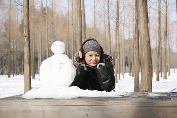 Asian beautiful woman building snowman in garden