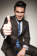 business man sitting while showing the thumbs up gesture