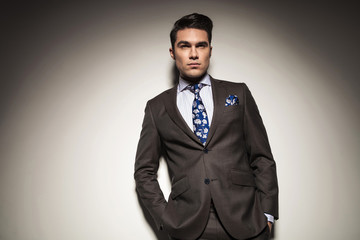 business man leaning on a grey wall