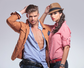 young casual couple posing on studio background