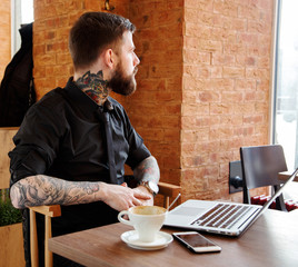Male with beard sitting in caffee shop and looking through a win
