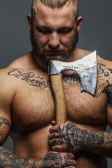 Brutal big man with tattooes and beard holding axe