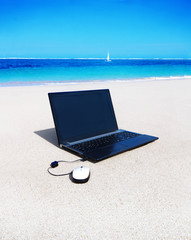 laptop with a mouse on the sand beach