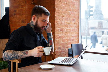 Male with tattoes talking on a phone in coffee shop