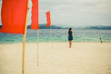 Woman on tropical beach with flags