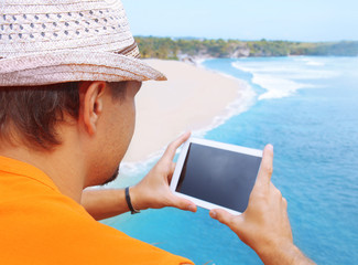 a man with tablet in hand on the beach