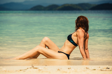 Sexy young woman lying on the beach