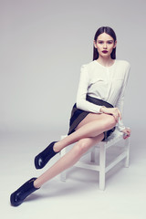 high fashion portrait of young elegant woman in black skirt and