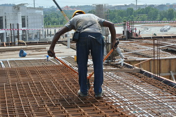 Construction workers using manual bolt cutter