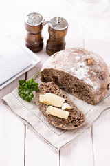 Freshly baked rye bread cob over white wooden background