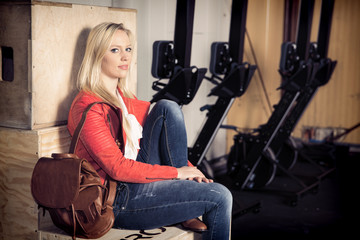 woman portrait - woman sitting on a box in a fitness studio