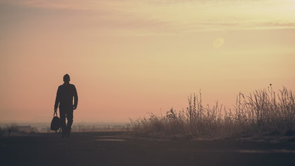 A man with a bag on the road. Cinema frame. Color correction.