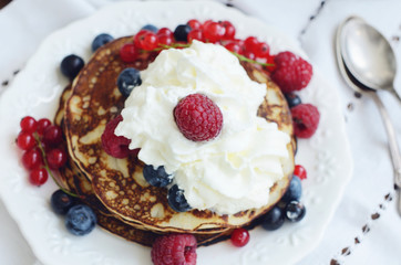 Homemade thin pancakes with whipped cream and fresh berries
