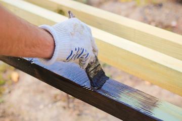 A man paints paint boards old tassel