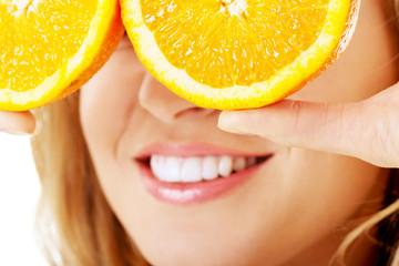 Close up woman holding oranges on eyes