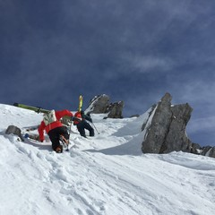 Two skiers climbing up a mountain carrying skis in Austria