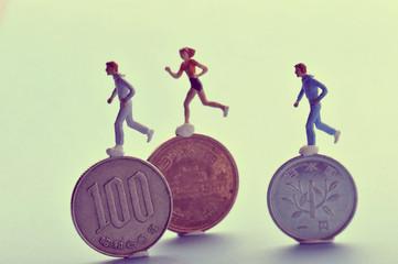 お金の上で競争して走っている人間のミニチュア