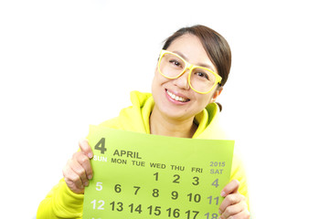 4月のカレンダーを持っている女性