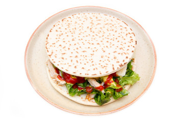 Flatbread with chicken and salad on white background top view
