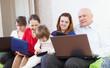 family enjoys on sofa with few laptops