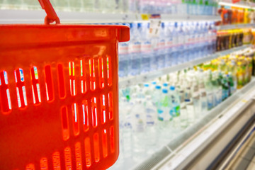 Shopping with red plastic basket in beverage department of super