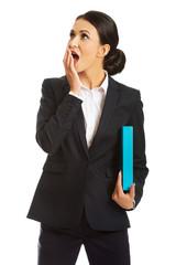 Shocked businesswoman holding a binder