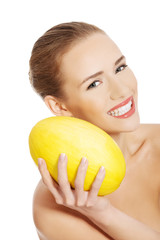 Portrait of nude woman holding yellow mango