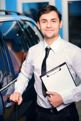 Car service manager posing with a clipboard