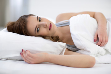 Portrait of attractive cute woman lying on the bed