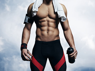 Strong athletic man on blue sky background