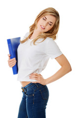 Side view of woman with back pain holding a binder