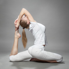 young beautiful woman doing yoga on gray background