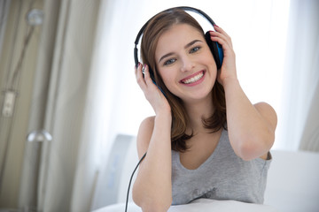 Portrait of a smiling woman with headphones at home