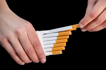Packs of cigarettes and hand isolated on black background