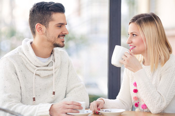 Young couple sitting in a cafe drinking coffee and tea