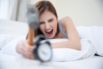 Woman not wanting to get up, taking a hammer to her alarm clock